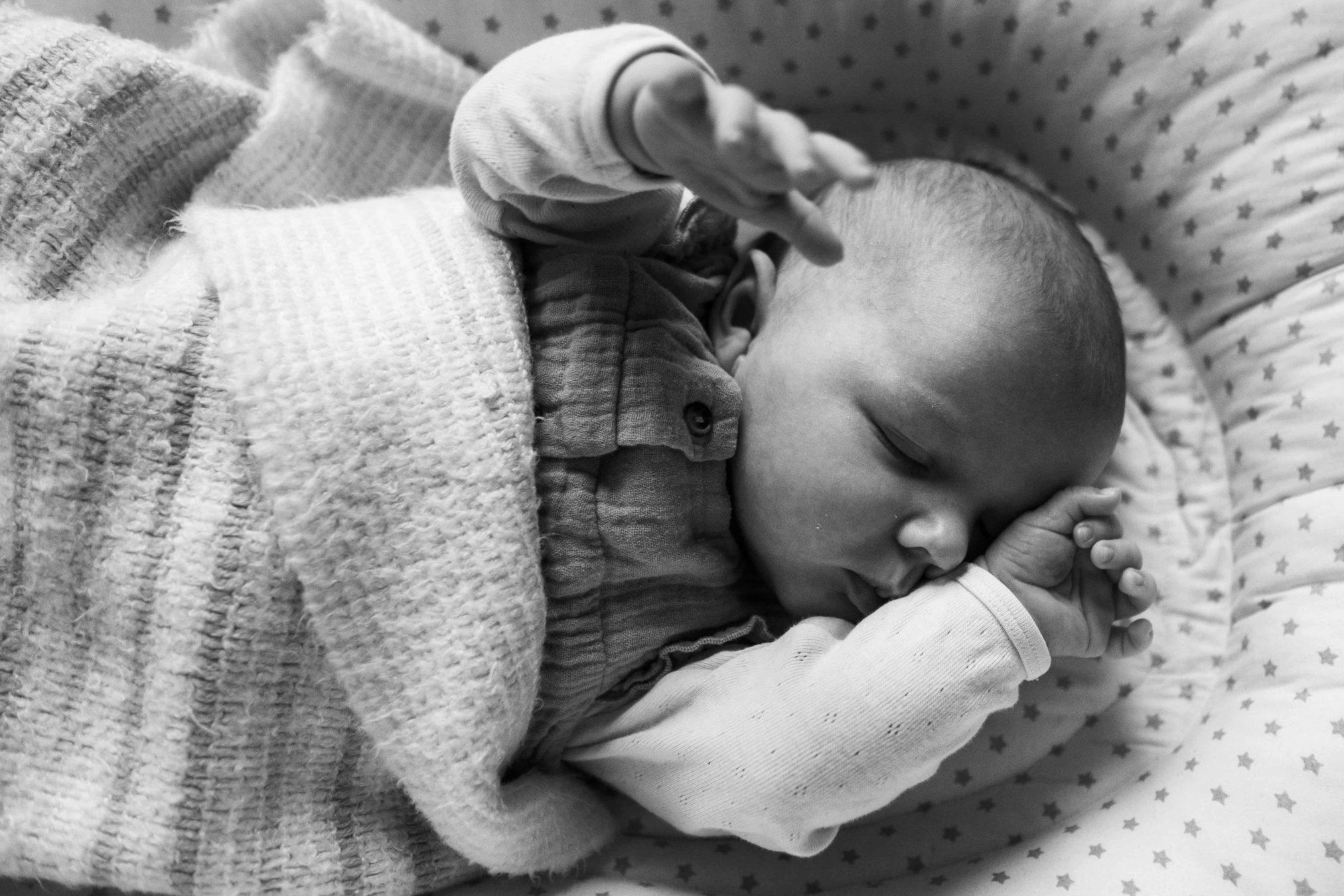 ein Baby liegt in einem Bettchen, es hält die Hände nach oben, es ist eingewickelt in einer Decke, es hat die Augen geschlossen, es neigt sich das Gesicht an ihren Arm