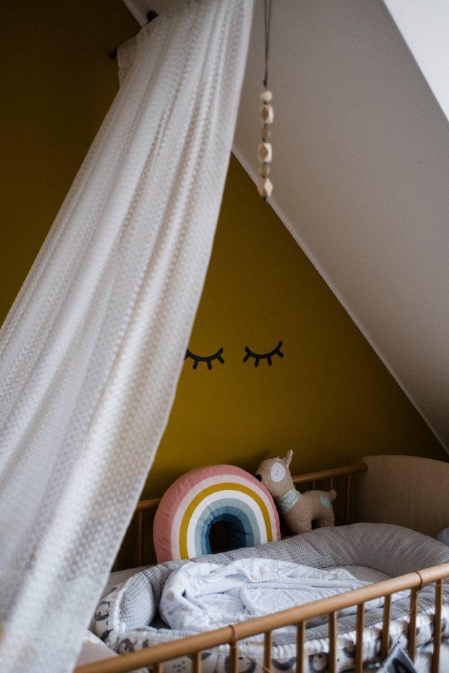 unter einer Dchschräge steht ein Kinderbett aus Holz, an der senfgelben Wand neben dem Bett kleben 2 geschlossene Augen, über dem Bett hängt ein heller Betthimmel, in dem Bettchen liegt ein Stillkissen, ein Regenbogenkissen und ein Lamastofftier