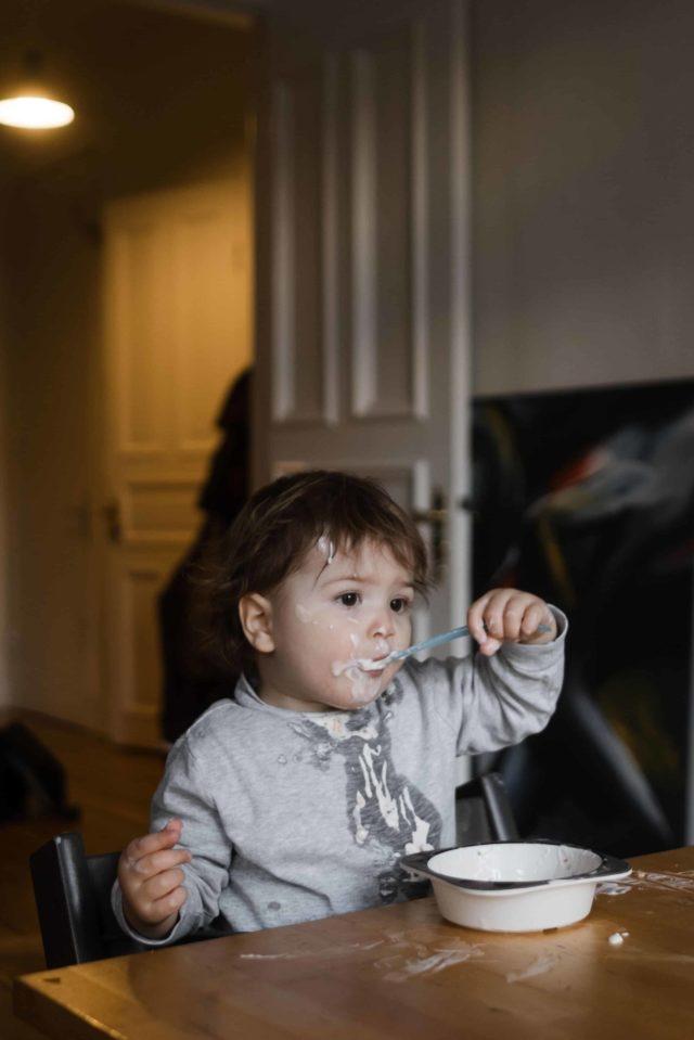 ein Kleinkind sitzt an einem Küchentisch, es hält sich einen kleinen Löffel in den Mund, vor dem Kind steht eine Schüssel mit Joghurt, das Gesicht des Kindes ist voll mit Joghurt, sowie der Tisch