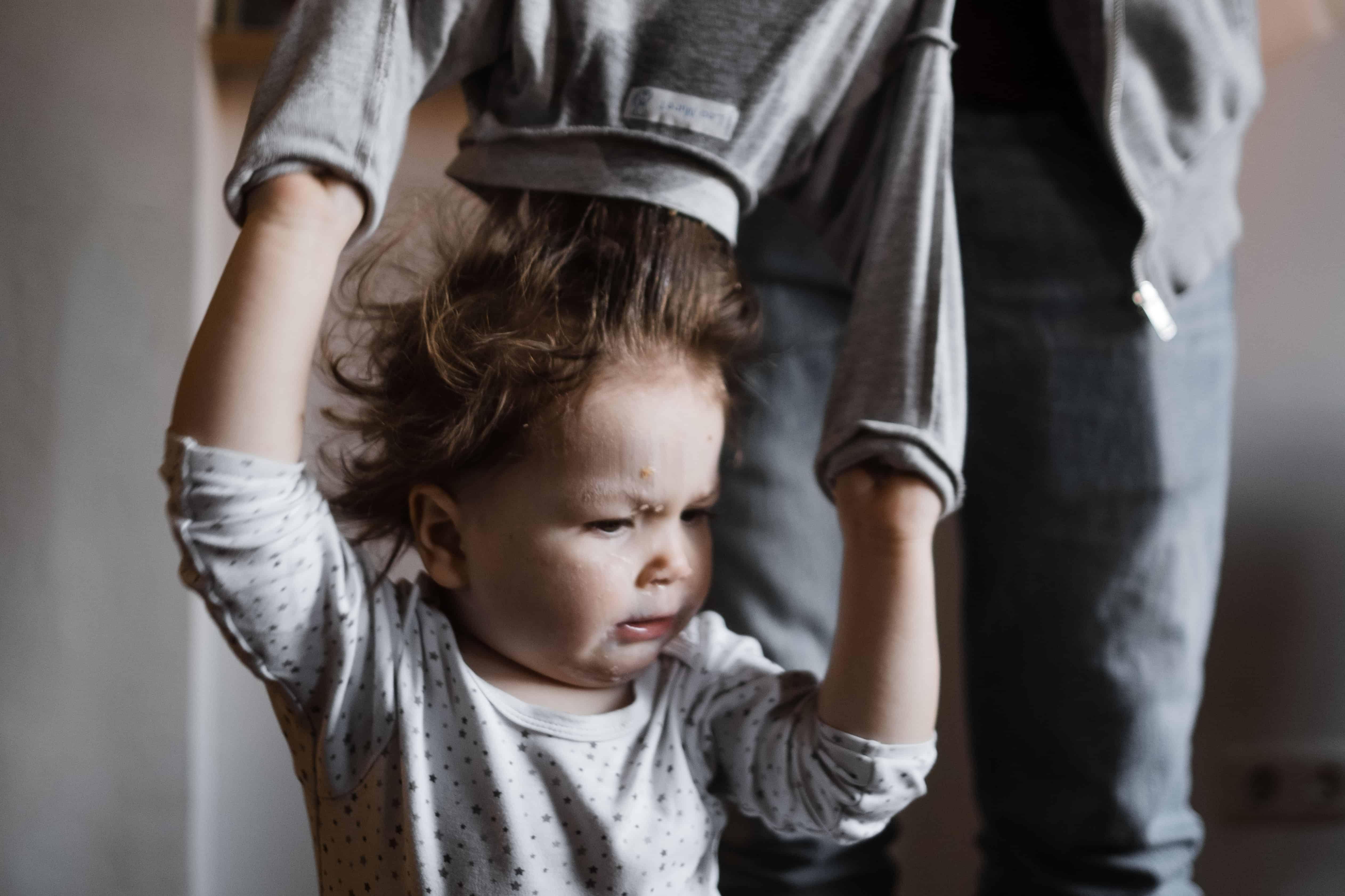 einem Kleinkind wird der dreckige Pullover über den Kopf gezogen, das Kind hebt die Arme dabei, man sieht das Gesicht des Kindes, es schaut nicht begeistert, hinter dem Kind steht der Vater, der dem Kind den Pullover auszieht