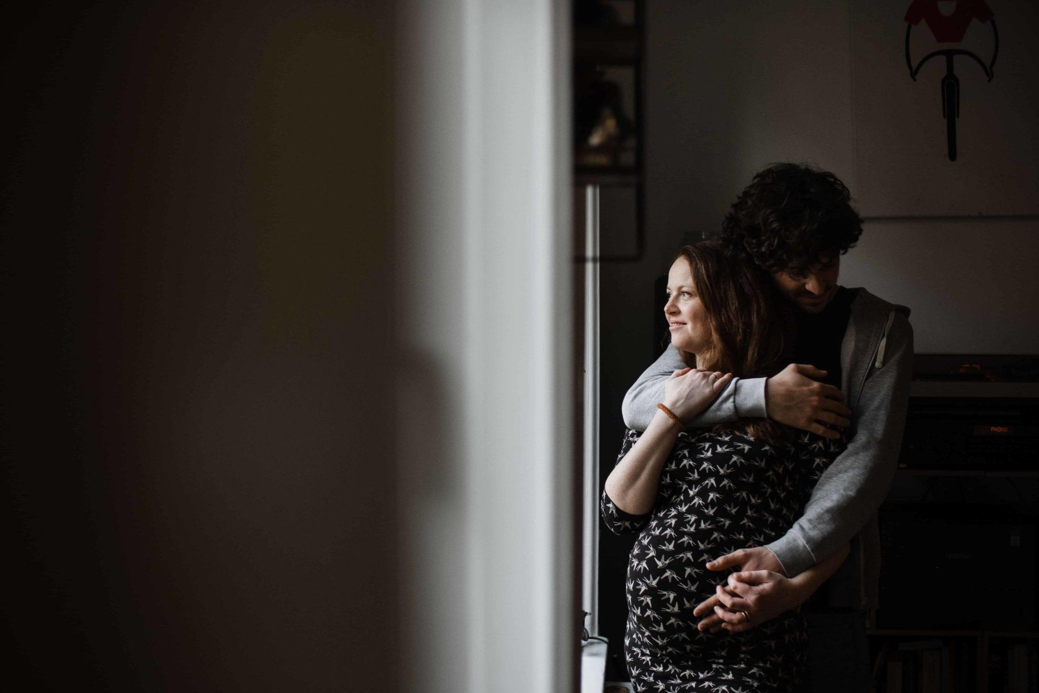 ein Mann hält seine Frau in dem Armen, den Arm hält er um ihren Hals, die andere Hand hält er an den Bauch der schwangeren Frau, die Frau schaut hinaus in die Ferne, sie stehen an einem Fenster, der Mann schaut an der Schulter der Frau vorbei auf den Boden, die Frau hält ihre Hand an den Arm des Mannes
