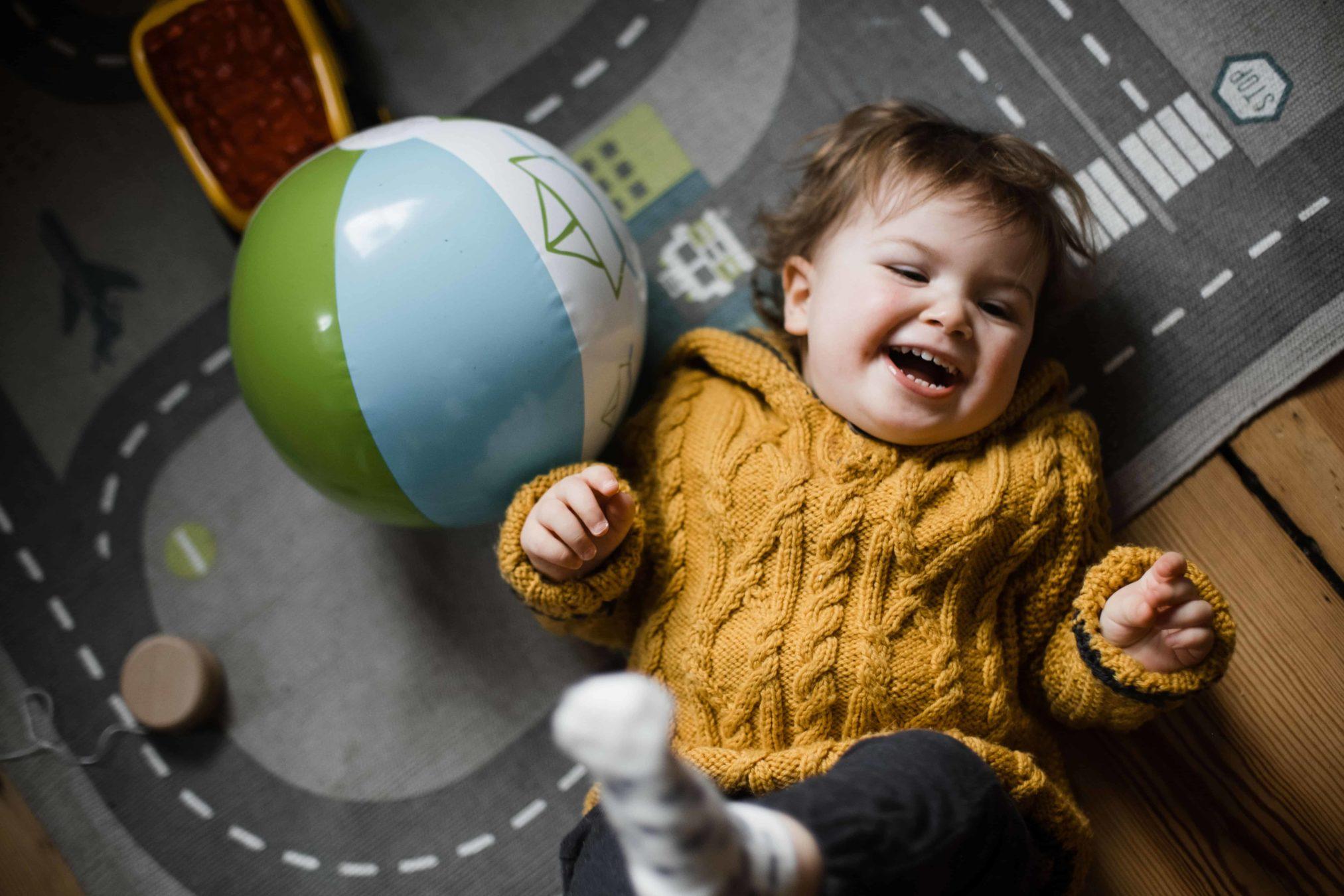 ein Kleinkind liegt mit dem Rücken auf einem Spielteppich, auf dem Straßen sind, es lacht und hebt dabi die Beine hoch, das Kind trägt einen gelben Strickpullover, neben dem Kind liegt ein aufgeblasener Gummiball