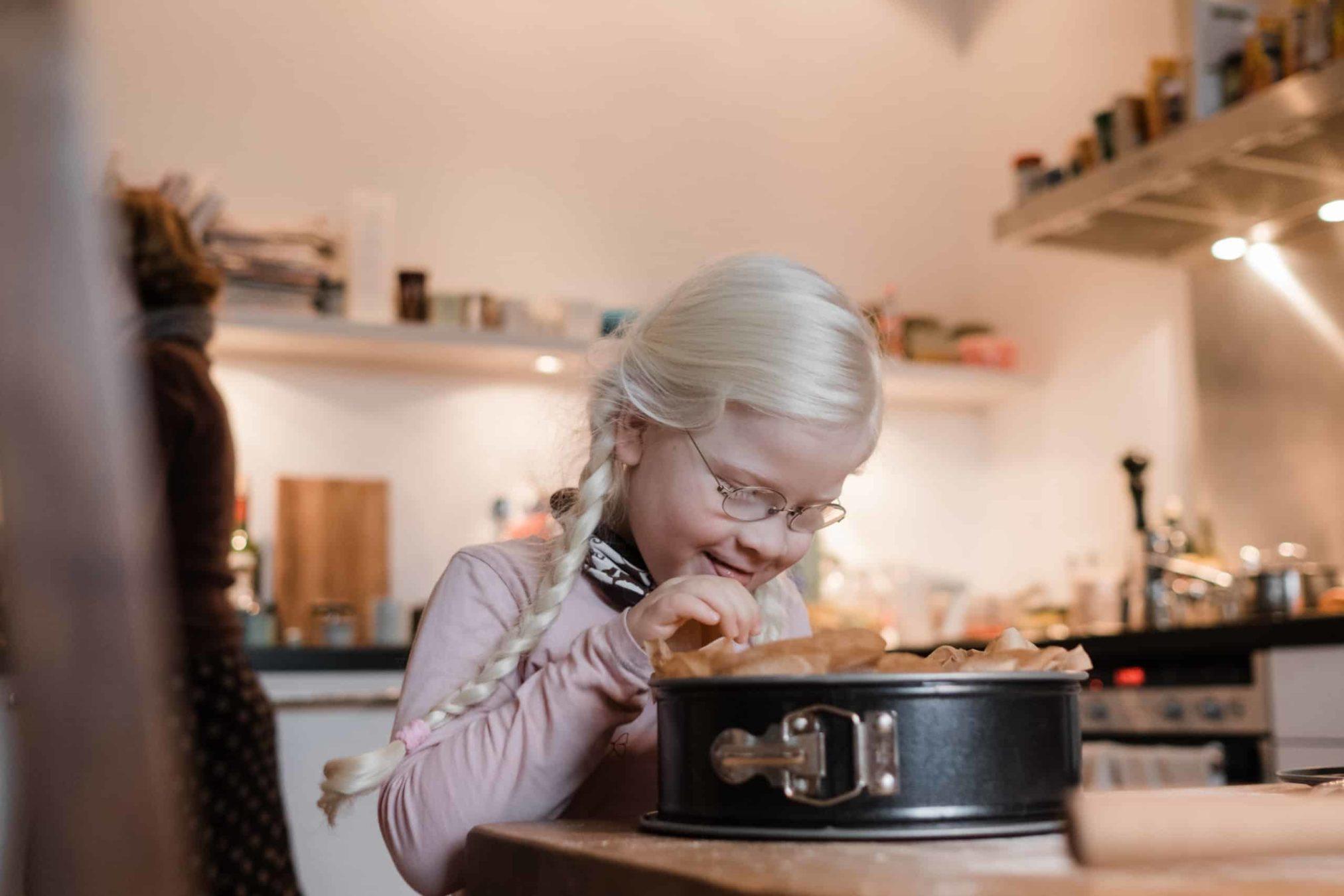 ein Mädchen steht an einem großen Küchentisch, sie schaut in eine Springform, die mit Backpapier ausgelegt ist, sie hat 2 Zöpfe und eine Brille, sie grinst, ihre Hand hält sie in die Springform