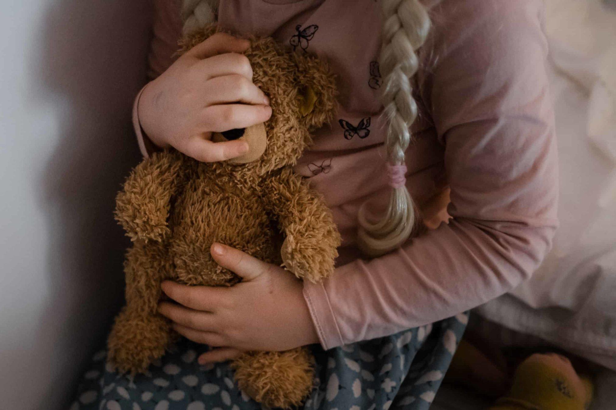 ein Mädchen hält einen braunen Teddybären in ihren Händen, sie trägt einen Rock, einen Pullove und 2 Zöpfe