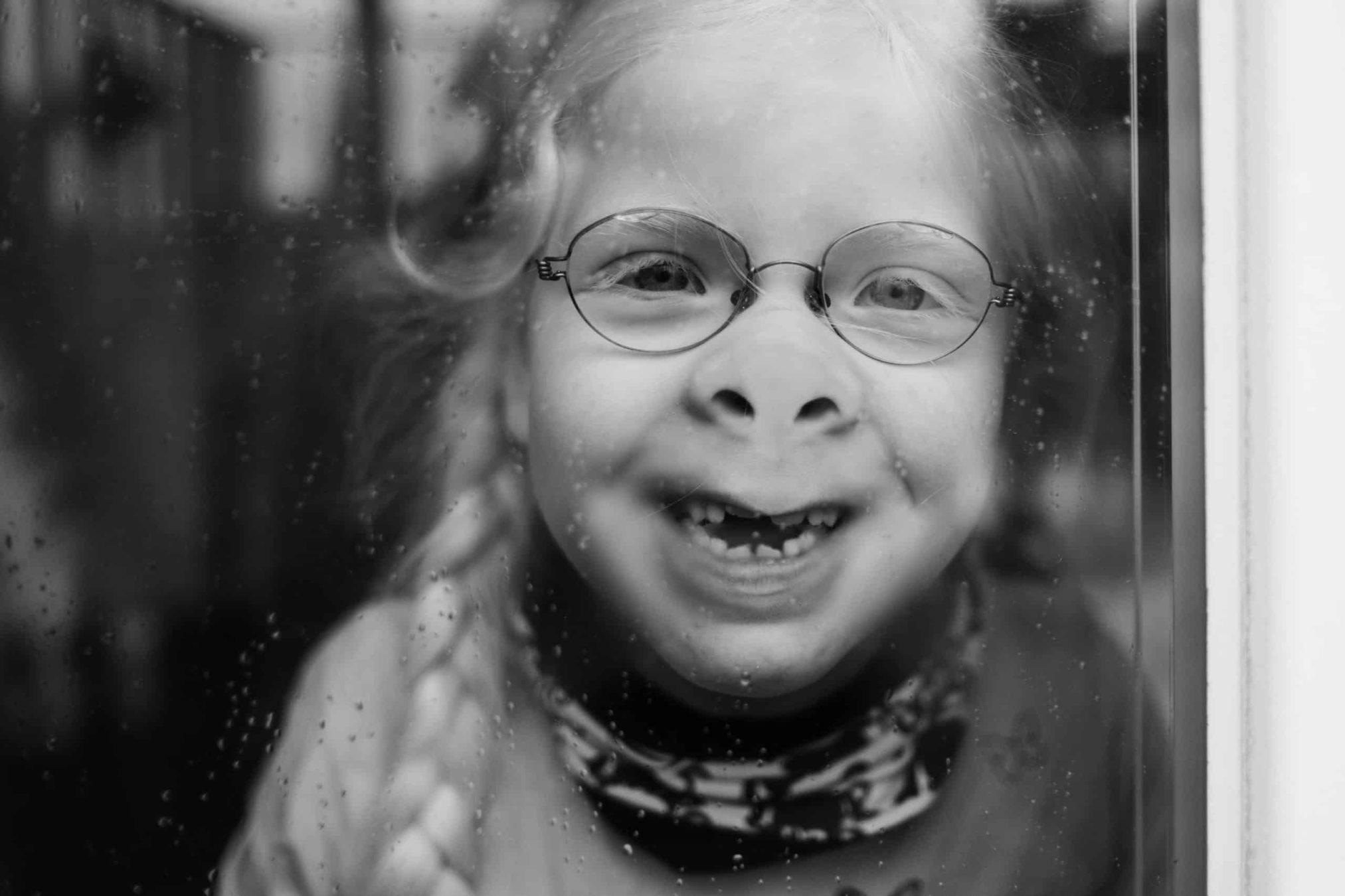 ein Mädchen mit Brille und 2 Zöpfen drückt ihr Gesicht gegen eine Fensterscheibe, sie hat dadurch eine platte Nase
