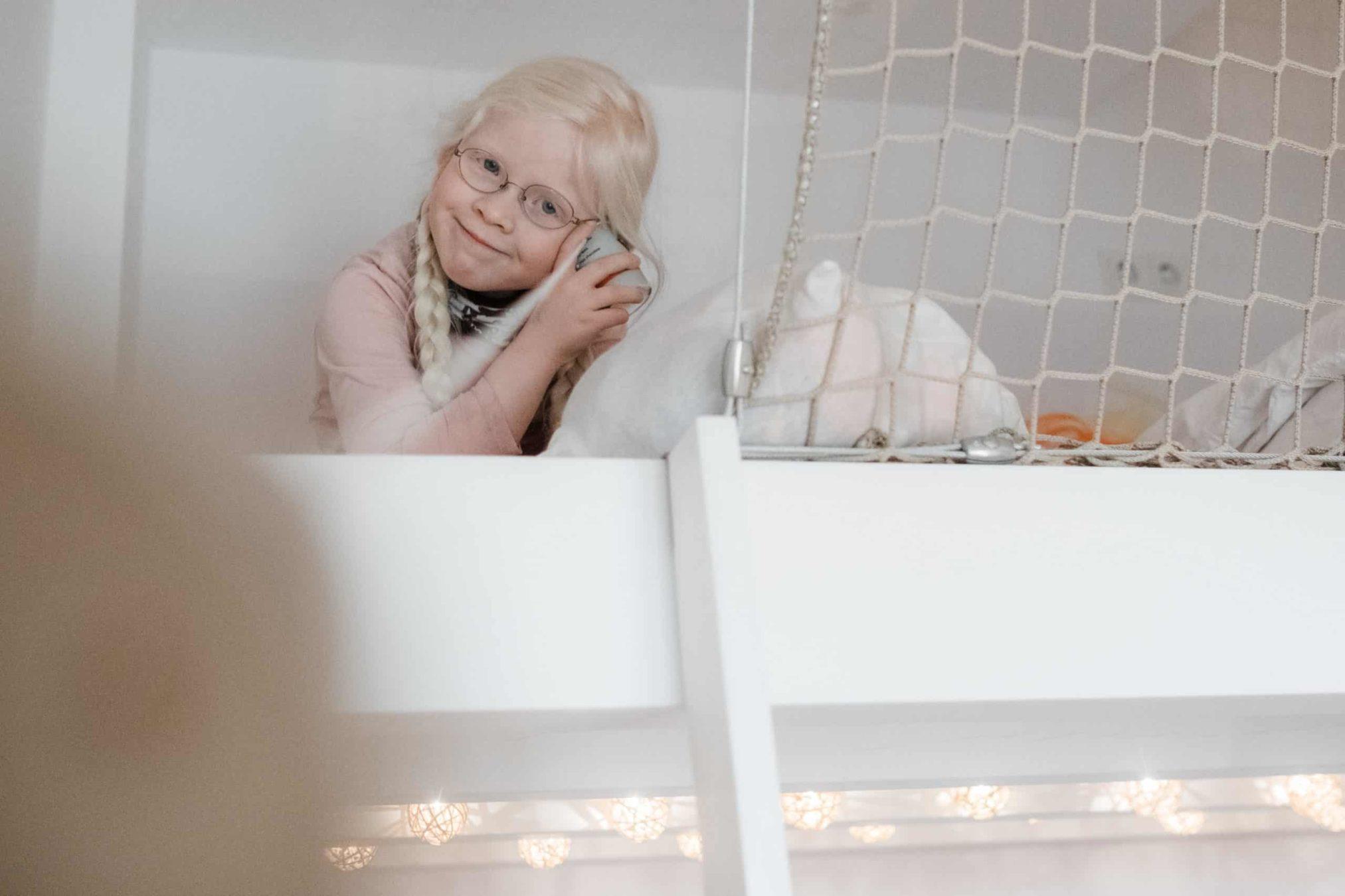 ein Mädchen sitzt auf einem Hochbett, sie trägt 2 Zöpfe und eine Brille, sie hält sich ein Kuscheltier an die Wange und grinst