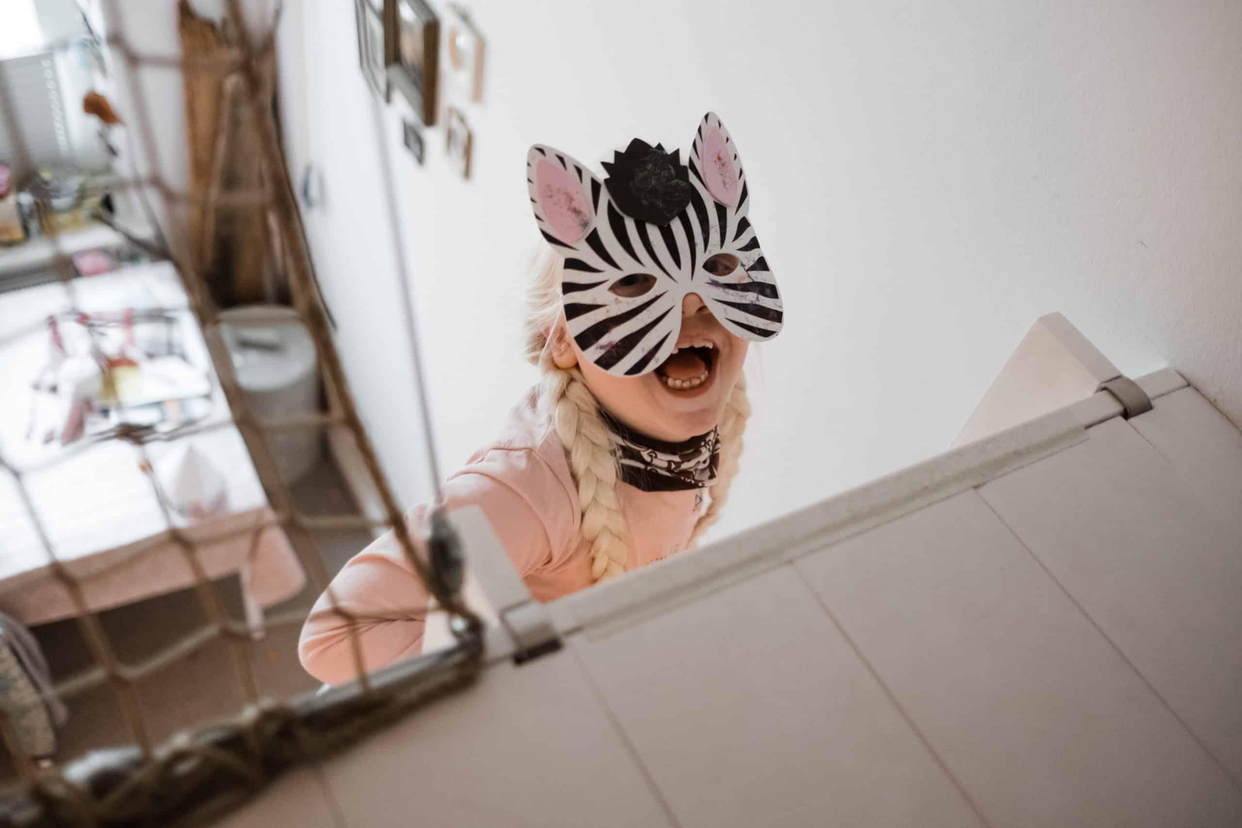 ein Mädchen trägt eine Zabramaske vor den Augen, sie hält ihren Mund auf und schaut nach oben