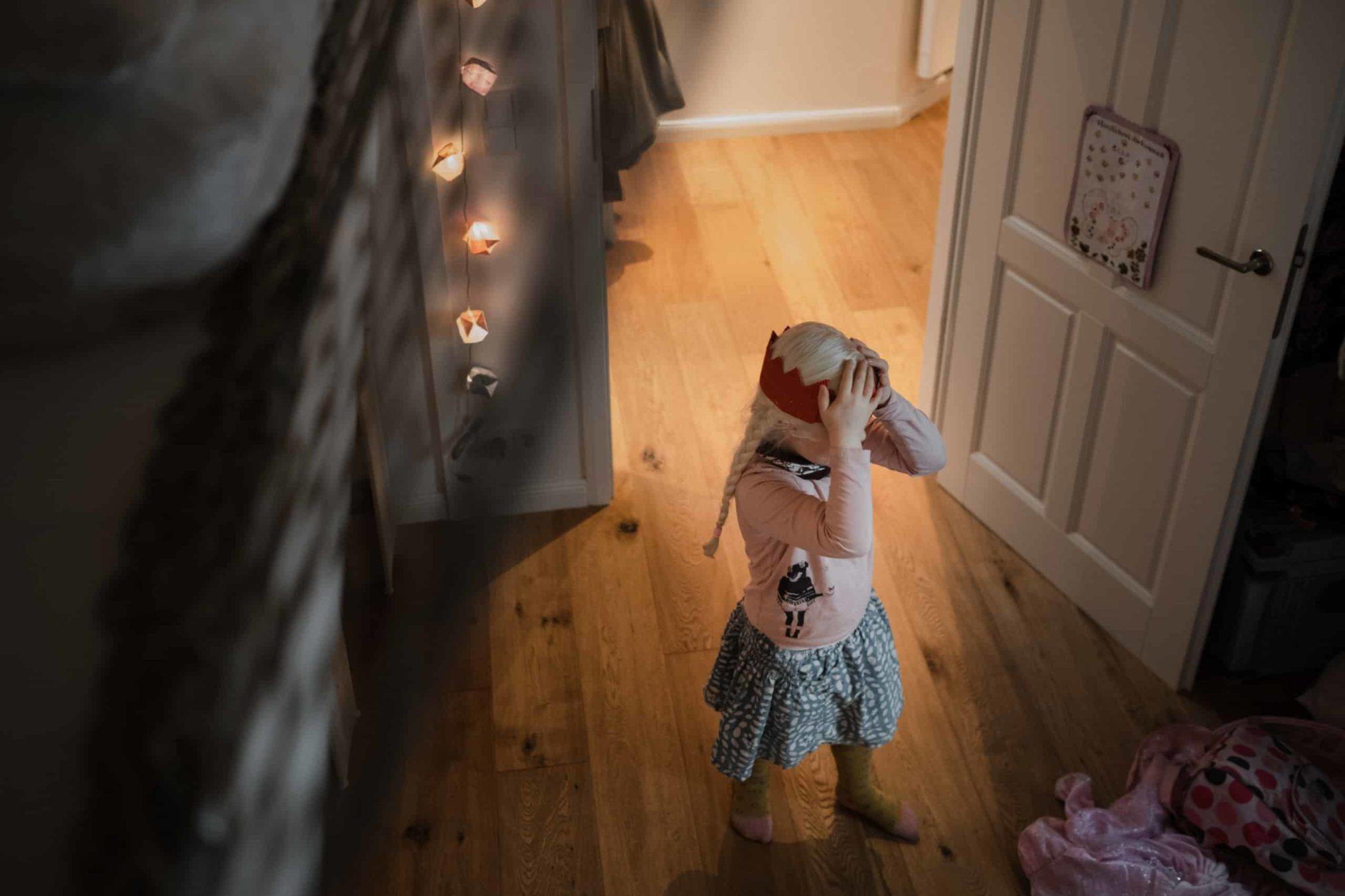 ein Mädchen steht in ihrem Kinderzimmer, sie trägt einen Rock und einen Pullover, sie hat eine rote Pappkrone auf den Kopf, die sie mit ihren Händen festhält, die Tür zu dem Zimmer steht auf, in dem Zimmer leuchtet eine Lichterkette