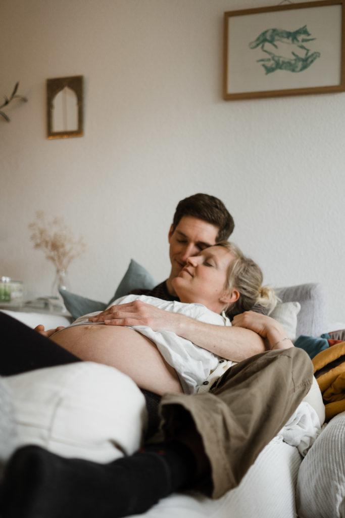 ein Mann und eine Frau liegen auf einem Sofa in einem Wohnzimmer, die Frau ist schwanger, sie liegt in den Armen des Mannes, beide haben geschlossene Augen