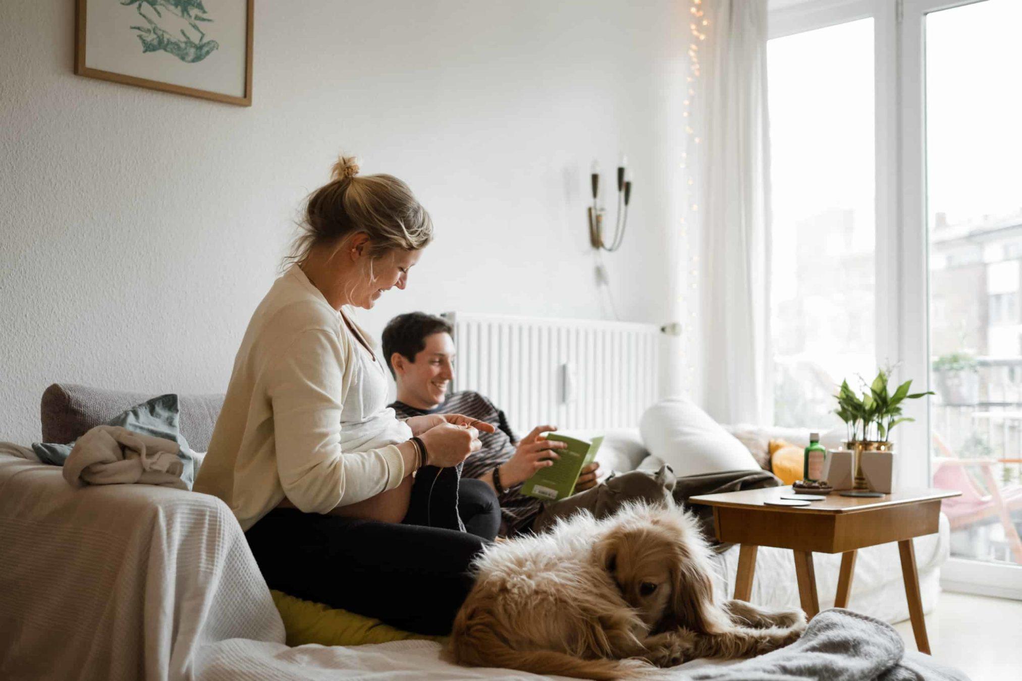 ein Mann und eine schwangere Frau sitzen auf einem Sofa in einem Wohnzimmer, die Frau ist schwanger, sie strickt, der Mann sitzt über Eck neben ihr, er blättert in einem Buch, neben der Frau sitzt ein Hund