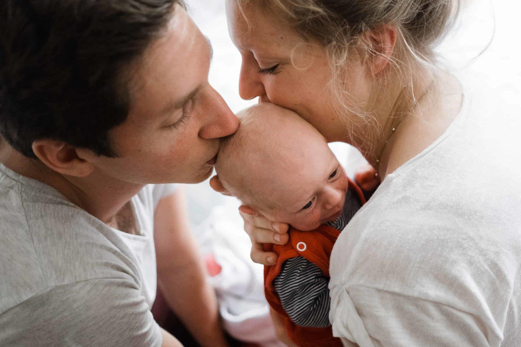 eine Frau hat ein Baby auf dem Arm, sie küsst das Baby auf dem Kopf, neben ihr steht ein Mann, der ebenfalls das Baby auf dem Kopf küsst