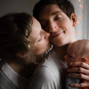 vor einem Fenster in einer Wohnung steht ein Mann, er hat ein Baby auf dem Arm, er hält seine Hand an den Kopf des Baby, er neigt seinen Kopf zu der Frau, die neben ihm steht, die Frau küsst ihn neben seinen Mund, beide haben geschlossene Augen