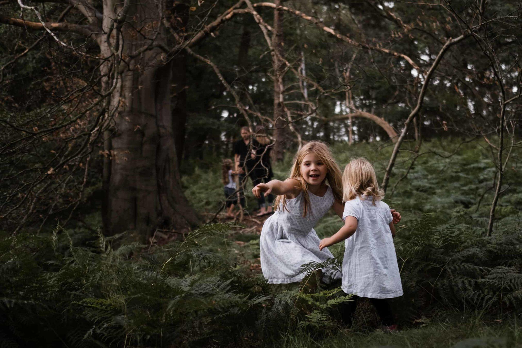 an einem großen Baum im Wald stehen 2 Mädchen, ein Mädchen zeigt mit ihrem Finger in die Ferne, im Hintergrund stehen der Vater und die Mutter ihrer Tochter