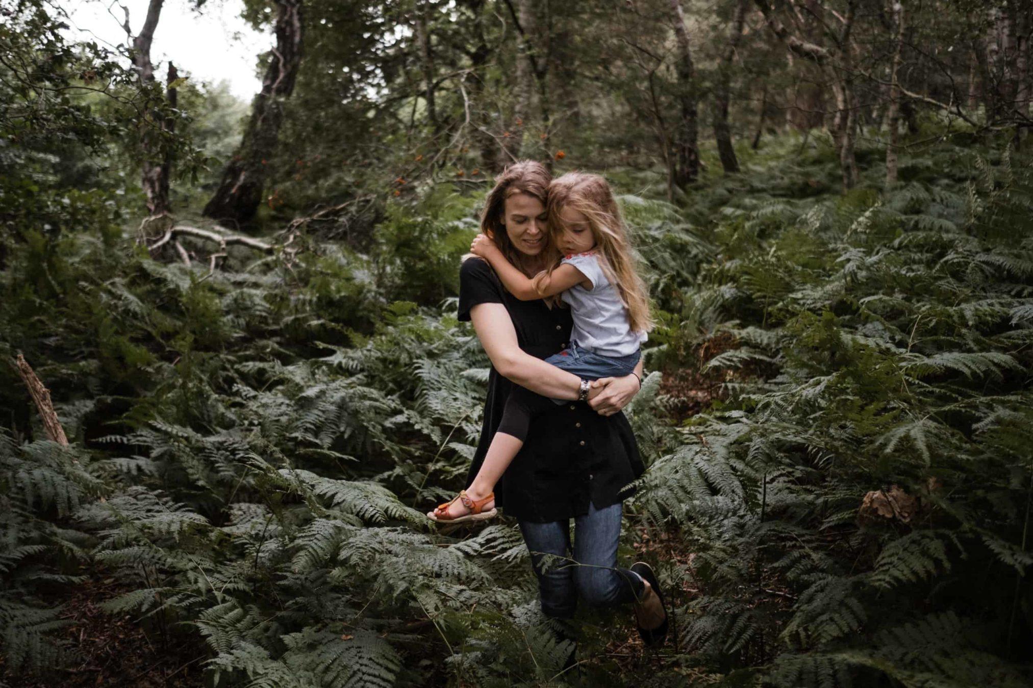 eine Mutter trägt ihre Tochter auf dem Arm durch einen Wald, der Boden ist mit großem Fahn bewachsen, die Tochter hält sich am Hals der Mutter fest