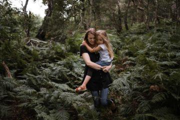 ein Vater hält sein Baby in den Armen, er hält sein Gesicht an den Kopf des Baby, hinter ihm steht seine Frau