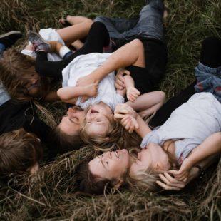 eine Mutter und ein Vater liegen mit ihren 3 Töchtern und ihrem Sohn auf einer Wiese, sie liegen kreuz und quer und auch übereinander, sie lachen