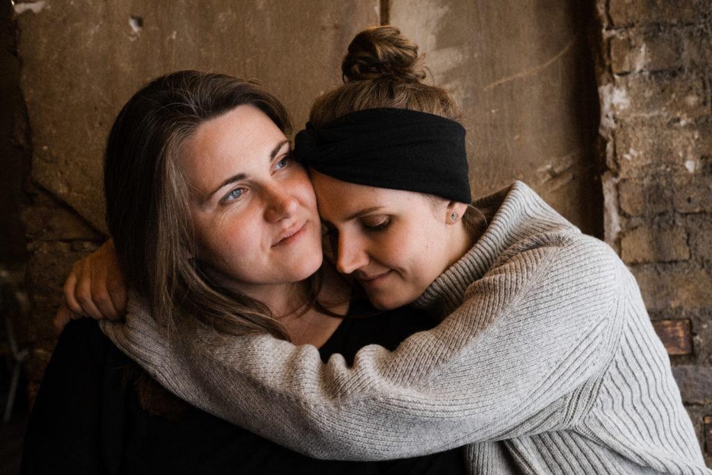 2 Frauen sitze vor einer Steinwand in einem Gebäude, eine Frau legt ihre Arme um den Hals der anderen, sie hält ihren Kopf an den Kopf der anderen Frau un schließt dabei die Augen