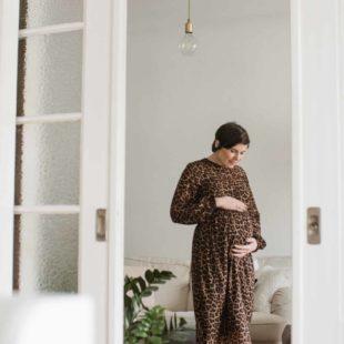 in einer offenen Schiebetür steht eine schwangere Frau in einem Leokleid, sie hält sich mit beiden Händen unter den Bauch, sie schaut auf ihren Bauch und grinst dabei, hinter ihr steht ein großes Sofa, über ihr hängt eine Glühbirne